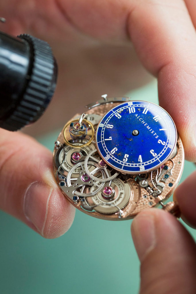 Closeup view of the Alchemists Cu29's movement, double barrels, hours dial and variable inertia balance