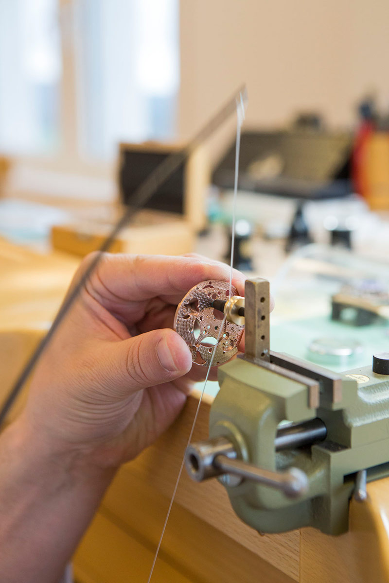 Picture of an Alchemists watchmaker working on the Cu29 movement's bottom plate